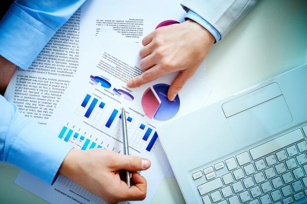 vista-superior-de-hombres-de-negocio-analizando-graficos-de-barras-y-un-portatil_1098-344