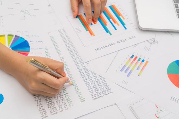 mujer-de-negocios-de-la-mano-con-graficos-financieros-y-la-computadora-portatil-en-la-ta_1232-3515